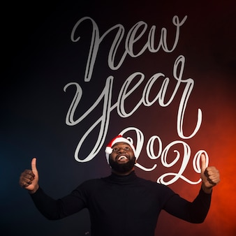 Happy man showing thumbs up and new year 2020 background