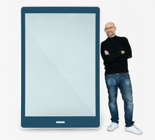 Happy man standing beside a tablet