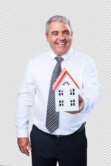 Happy mature man holding a house