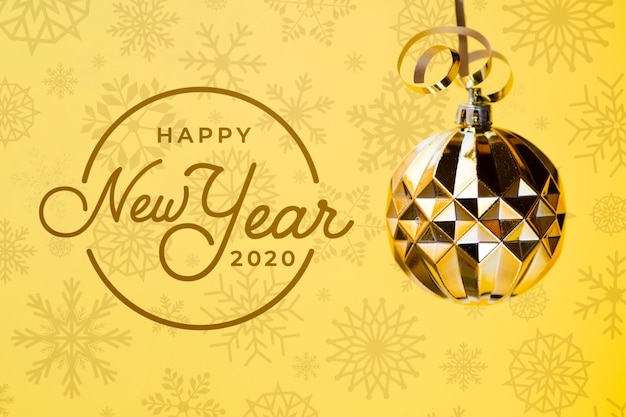 Happy new year 2020 with golden christmas ball on yellow background