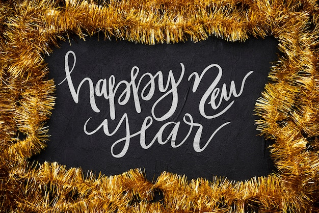 Happy new year handwriting lettering surrounded my tinsel