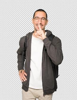 彼の指で身振りで示す沈黙を求める幸せな学生