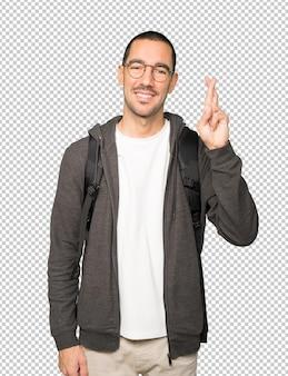 Счастливый студент делает жест скрещенными пальцами