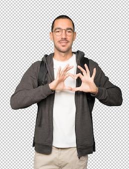 彼の手で愛のジェスチャーをしている幸せな学生