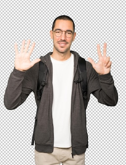 彼の手で8番のジェスチャーをしている幸せな学生