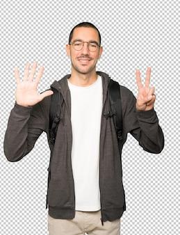 彼の手で7番目のジェスチャーをしている幸せな学生