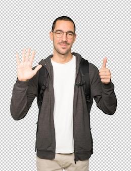 彼の手で6番目のジェスチャーをしている幸せな学生