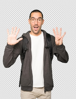 Happy student doing a number nine gesture with his hands
