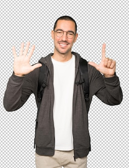 Happy student doing a number seven gesture with his hands