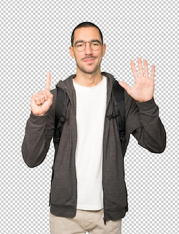 Happy student doing a number six gesture with his hands