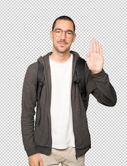 彼の手のひらで停止のジェスチャーをしている幸せな学生