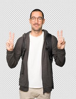 그의 손가락으로 승리 제스처를 만드는 행복 한 학생