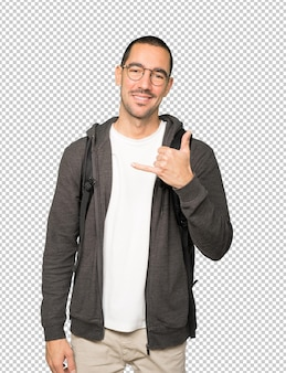 Happy student making a gesture of calling with the hand