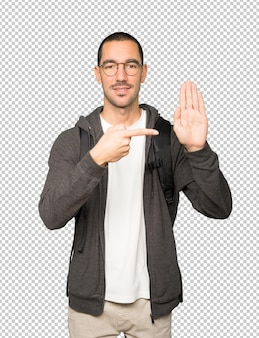 Happy student making a gesture of stop with his palm