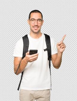 指摘して携帯電話を使用して幸せな学生