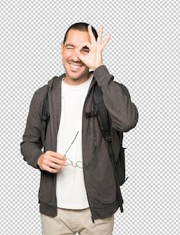 쌍안경처럼 그의 손을 사용하여 행복한 학생