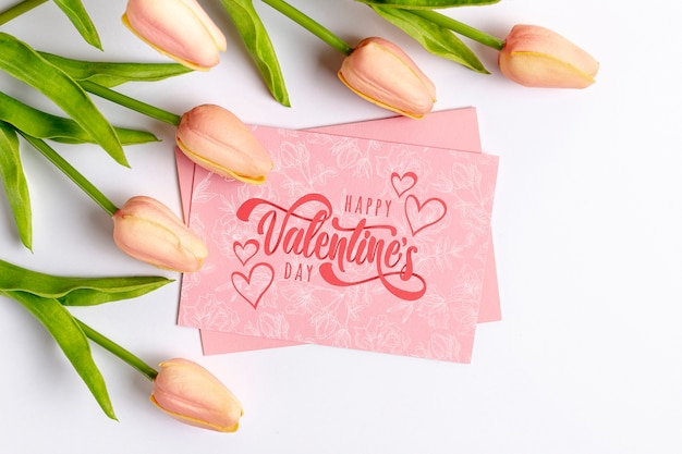 Happy valentines day lettering on pink card next to tulips