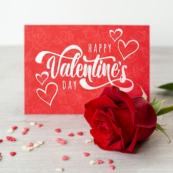 Happy valentines day lettering on red card with red rose