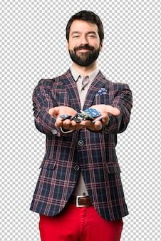 Счастливый одетый человек, держащий покерные фишки