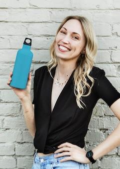Счастливая женщина, несущая макет термальной бутылки