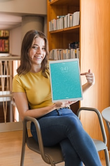 Happy woman holding tablet mockup in library
