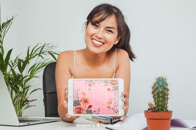 Счастливый женщина с макетом планшета в офисе
