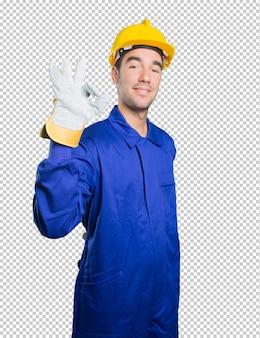 Счастливый рабочий, делая жест утверждения на белом фоне