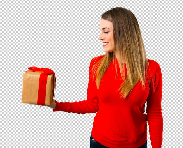 Happy young blonde woman holding a gift