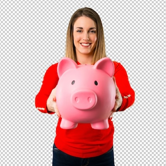 Happy young blonde woman holding a piggybank
