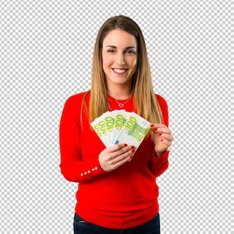 Счастливая молодая белокурая женщина принимая много денег