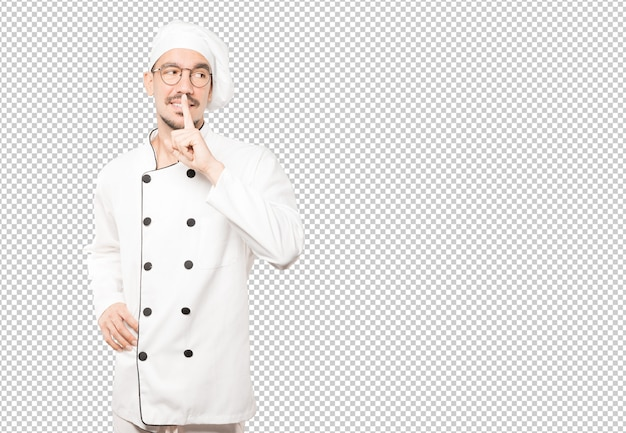 Happy young chef asking for silence gesturing with his finger