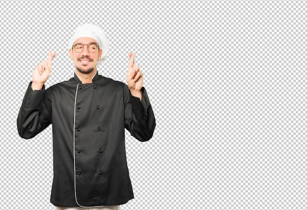 Счастливый молодой шеф-повар делает скрещенные пальцы жест