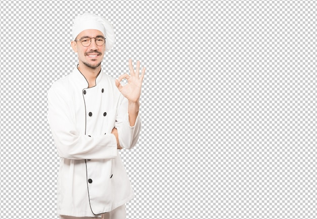 Happy young chef doing an all right gesture