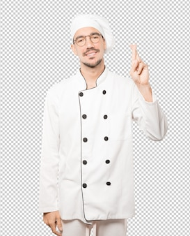 Happy young chef doing a crossed fingers gesture