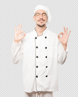 Happy young chef doing a gesture of meditation