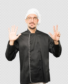 Happy young chef doing a number eight gesture with his hands