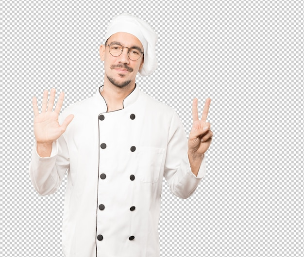 Happy young chef doing a number seven gesture with his hands