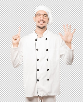 Happy young chef doing a number six gesture with his hands