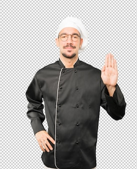 Счастливый молодой шеф-повар делает жест остановки ладонью