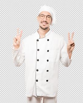 그의 손가락으로 승리 제스처를 만드는 행복 한 젊은 요리사