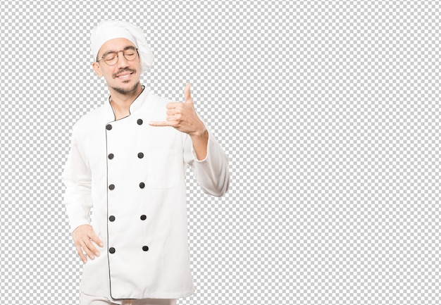 Happy young chef making a gesture of calling with the hand