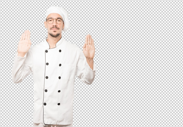 Happy young chef making a gesture of stop with his palm