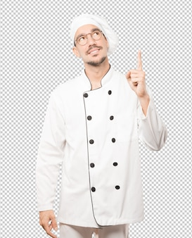 Happy young chef pointing up with his finger