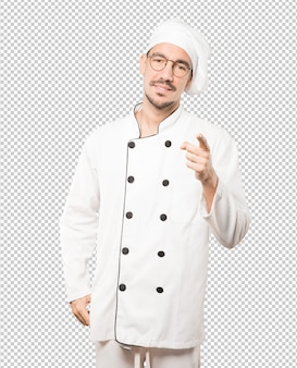 Happy young chef pointing at you with his finger