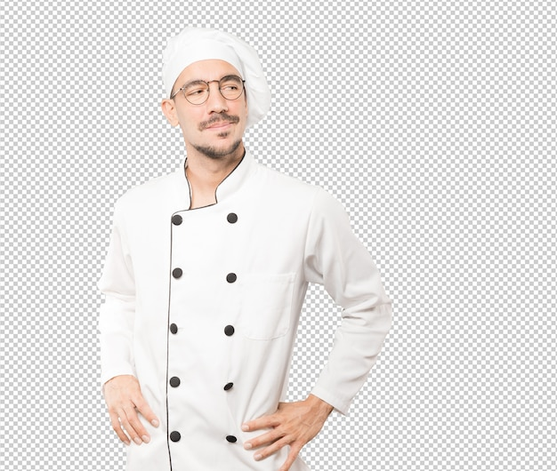 Happy young chef posing against background