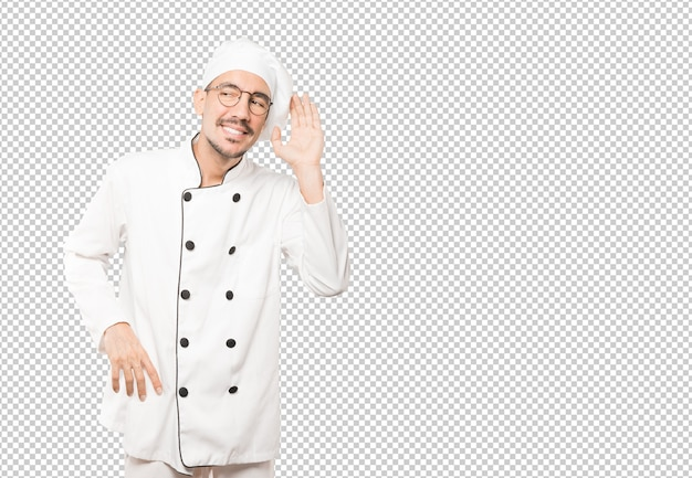 Happy young chef smiling and making a gesture of trying to hear something