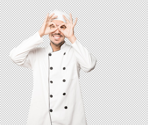 Happy young chef using his hands like a binoculars