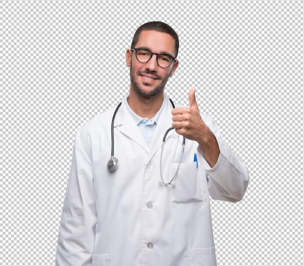 幸せな若い医者が大丈夫のジェスチャーをしている