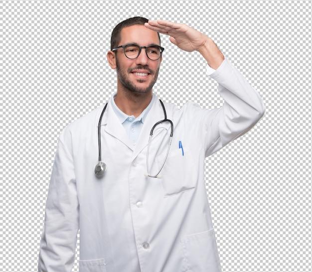 遠くを見るジェスチャーを持つ幸せな若い医者