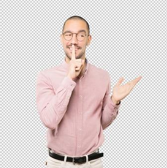 彼の指で身振りで示す沈黙を求めて幸せな若い男